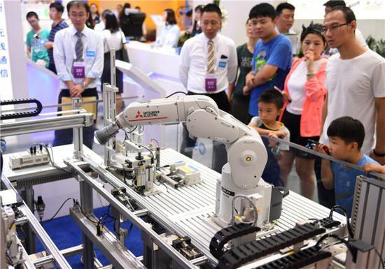 ↑观众在2018世界机器人大会上参观一款工业机器人(8月15日摄)。新华社记者 张晨霖 摄